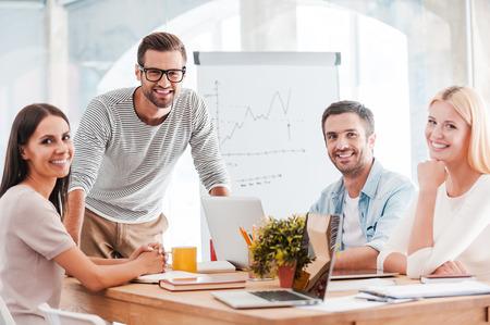 자신감 비즈니스 팀. 함께 책상에 앉아 웃 스마트 캐주얼 쾌활한 비즈니스 사람의 그룹