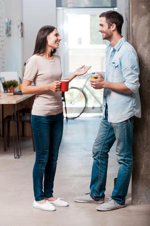 dos personas platicando: Pausa para el caf�. Longitud total de dos j�venes alegres hablar y sonre�r durante una pausa para el caf� en la oficina
