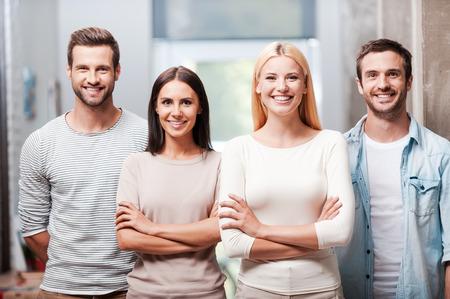 Jong en succesvol team. Vier jonge mensen in slimme vrijetijdskleding staan dicht bij elkaar en glimlachen bespreken