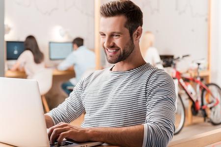 operarios trabajando: El trabajo con el placer. Apuesto joven que trabaja en la computadora portátil y sonriendo mientras sus colegas que trabajan en segundo plano