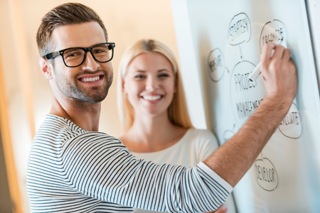 working place: Planning business together. Confident young man and woman looking at camera and smiling while both standing near whiteboard in office