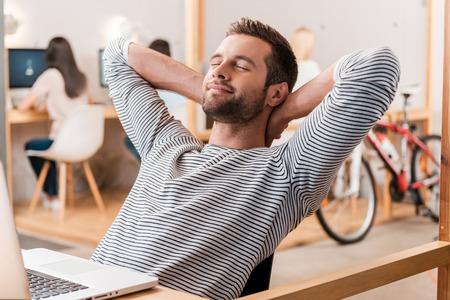 descansando: Tomarse el tiempo para una escapada minutos. Alegre joven la mano detrás de la cabeza y manteniendo los ojos cerrados mientras está sentado en su lugar de trabajo con sus colegas que trabajan en segundo plano
