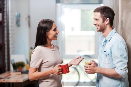 Spendera en trevlig kaffepaus. Två glada ungdomar som håller kaffekoppar och pratar när du står i kontor