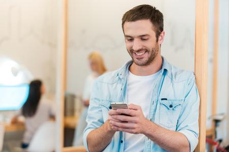 happy young: Estar conectado. Hombre joven feliz que mira su tel�fono m�vil y sonriendo mientras sus colegas que trabajan en segundo plano