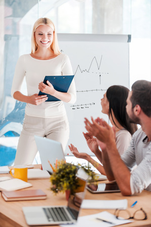 congratulating: Congratulating with success. Beautiful young woman standing near whiteboard and smiling while her colleagues sitting at the desk and applauding