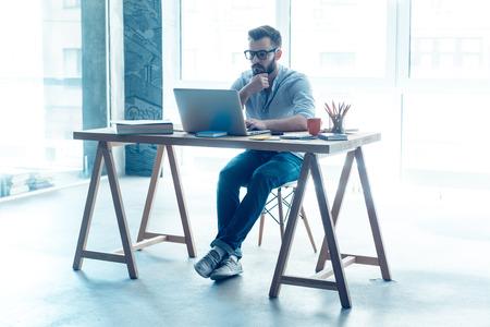trabajando: Sentirse cómodo en su lugar de trabajo. Hombre de barba joven concentrado trabaja en la computadora portátil mientras está sentado en su lugar de trabajo en la oficina