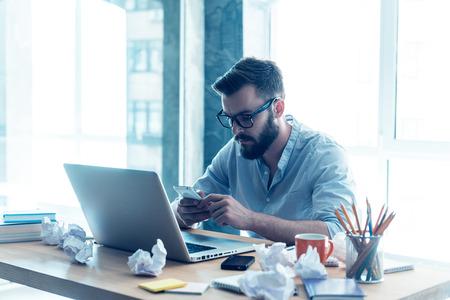 trabajo oficina: La concentración total en el trabajo. Concentrado joven barba mirando a su teléfono móvil mientras se está sentado en su lugar de trabajo en la oficina Foto de archivo
