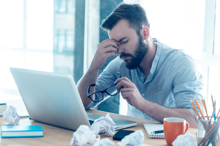 emotional stress: Feeling exhausted. Frustrated young beard man massaging his nose and keeping eyes closed while sitting at his working place in office Stock Photo