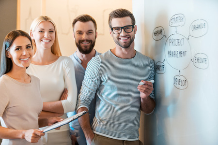 Young and successful team. Group of cheerful young business people in smart casual wear looking at camera and smiling while standing together near whiteboard Standard-Bild