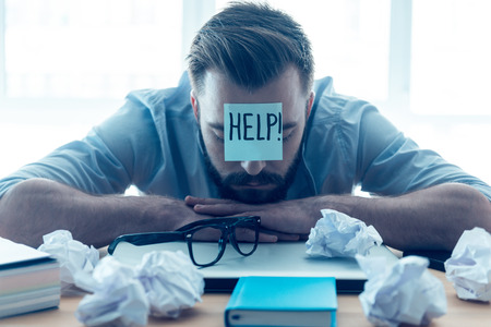 He needs help. Hopeless young beard man with adhesive note on his forehead leaning at the desk and keeping eyes closed while sitting at his working place in office Фото со стока