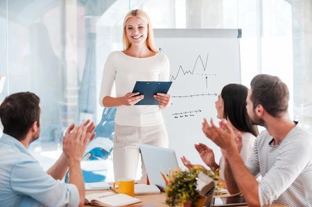 素晴らしいプレゼンテーションを!陽気な若い女性ホワイト ボードの近くに立って、彼女の同僚の机に座っていると拍手しながら笑みを浮かべて
