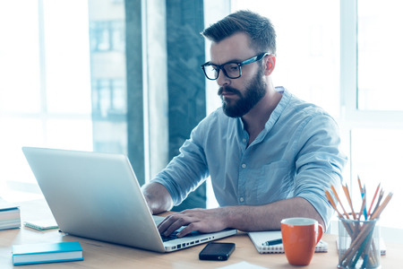 Auf die Arbeit konzentriert. Konzentrierte junge Bart Mann am Laptop, während sitzt an seinem Arbeitsplatz im Büro