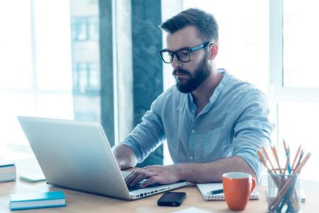 soustředění: Se soustředil na práci. Koncentrovaný mladý vousy muž pracuje na laptop, zatímco sedí na svém pracovním místě v kanceláři