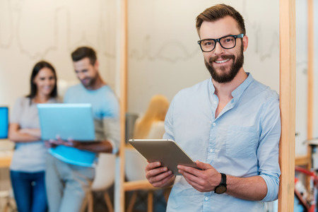 Confident IT expert. Cheerful young man holding digital tablet and smiling while his colleagues working in the background