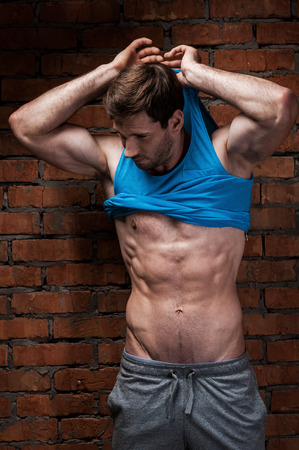 undressing: Man undressing. Handsome young muscular man taking off his tank top while standing against brick wall