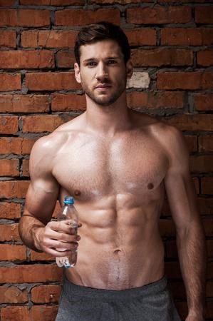 cuerpo hombre: Refrescante descanso. Hombre musculoso joven hermoso que sostiene una botella de agua en la mano mientras está de pie contra la pared de ladrillo
