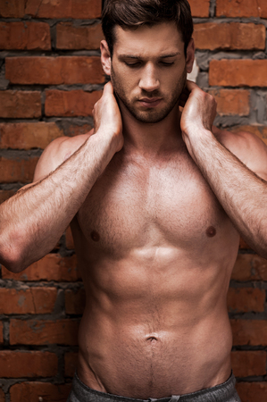 abdominal wall: My body is a reflection of my lifestyle. Handsome young shirtless man holding hands behind neck and keeping eyes closed while standing against brick wall