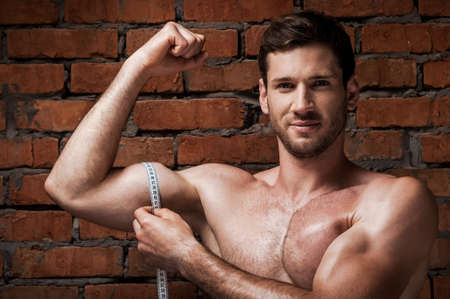 only the biceps: Measuring his perfect bicep. Smiling muscular man measuring his bicep with measuring tape while standing against brick wall Stock Photo