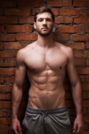 masculinity: Strength and masculinity. Handsome young muscular man posing while standing against brick wall