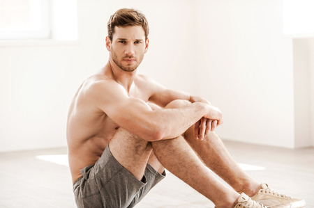 Rugged and handsome. Handsome young shirtless man in shorts sitting on the floor and looking at camera