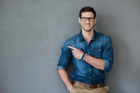 male models: Pointing copy space. Joyful young man pointing away and looking at camera while standing against grey background Stock Photo