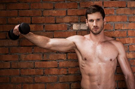 strength training: Showing his strength. Serious young muscular man training with dumbbells while standing against brick wall Stock Photo