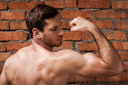 only the biceps: Showing his perfect bicep. Rear view of confident young muscular man posing while standing against brick wall