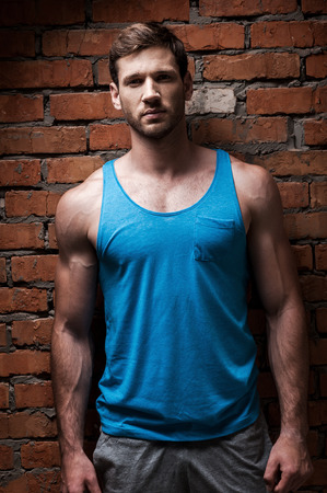 tank top: Fit and confident. Confident young muscular man posing while standing against brick wall