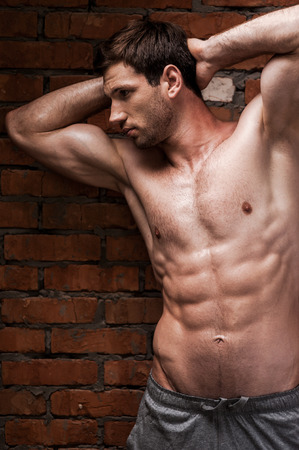 abdominal wall: Confident in his perfect body. Handsome young shirtless man holding hands behind head and looking away while standing against brick wall