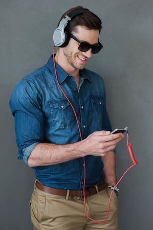audifonos: Disfrutar de la música favorita. Hombre joven alegre en auriculares sosteniendo reproductor de MP3 y mirarlo mientras está de pie contra el fondo gris Foto de archivo