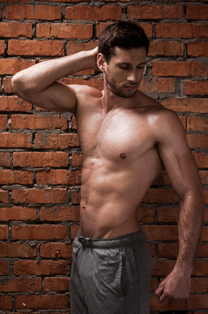 abdominal wall: He is just perfect. Handsome young muscular man posing while standing against brick wall Stock Photo