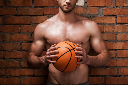 shirtless guy: Ready to play ball. Cropped image of young muscular man holding basketball ball while standing against brick wall