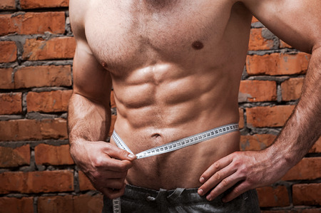 abdominal wall: Keeping his body fit. Close-up of muscular man measuring his waist with measuring tape while standing against brick wall