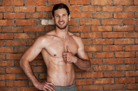 only the biceps: Looking good and feeling great. Cheerful young shirtless man holding thumb up and smiling while standing against brick wall Stock Photo