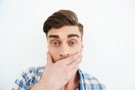 no idea: No way! Shocked young man covering mouth with hand and looking at camera while standing against white background