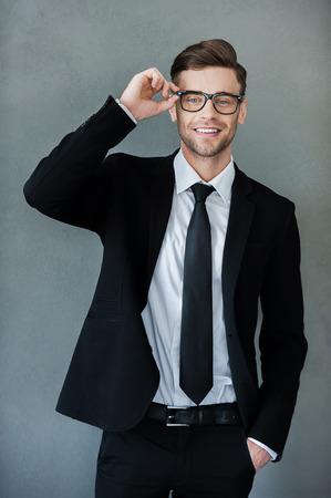 Klaar om zaken te doen. Happy jonge zakenman aanpassing van zijn brillen en kijken naar de camera terwijl je tegen een grijze achtergrond Stockfoto