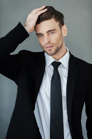Légant beau. Beau jeune homme d'affaires de toucher ses cheveux et regardant la caméra en se tenant debout sur fond gris Banque d'images - 41560071