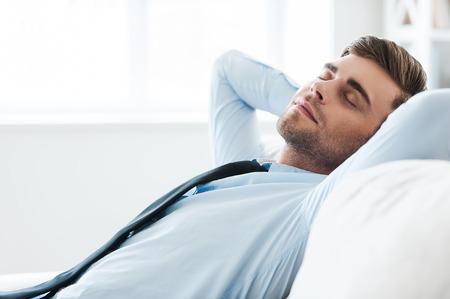 Tiempo para relajarse. Hombre de negocios de la mano detrás de la cabeza y mantener jóvenes guapos ojos cerrados mientras está sentado en el sofá Foto de archivo - 41560073