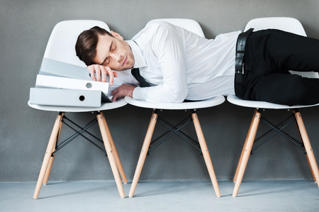 tired person: Tired after hard working. Tired young man keeping eyes closed while laying on chairs against grey background