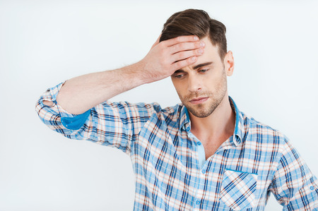 hopelessness: Feeling hopelessness. Frustrated young man in shirt touching forehead while standing against white background Stock Photo