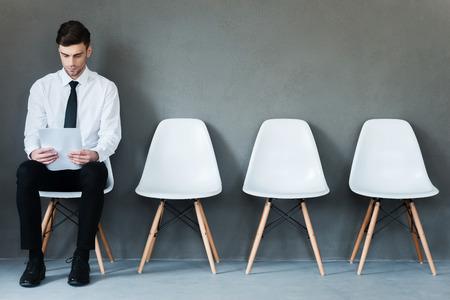 entrevista: A la espera de la entrevista. Joven hombre de negocios confía en la celebración de papel mientras se está sentado en la silla contra el fondo gris Foto de archivo
