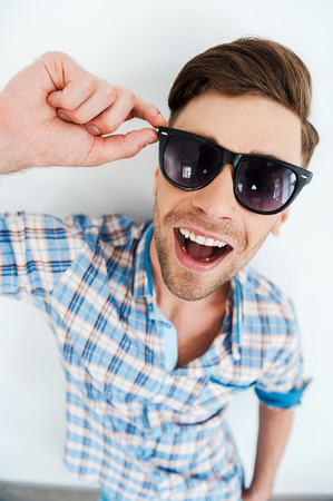 cool man: Cool and trendy. Top view of cheerful young man adjusting eyewear while standing against white background Stock Photo