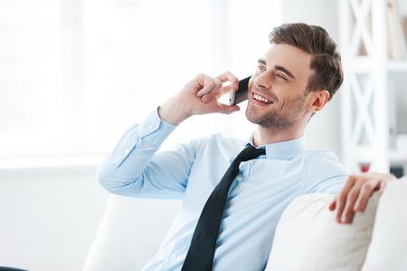여러분의 의견을 위대하다! 쾌활 한 젊은 사업가 휴대 전화에 얘기하는 소파에 앉아있는 동안 미소