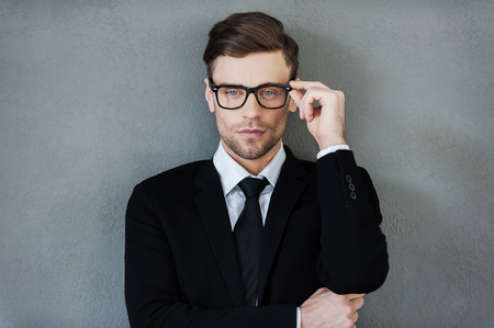 stylish men: Stylish handsome. Confident young businessman adjusting his eyewear and looking at camera while standing against grey background Stock Photo