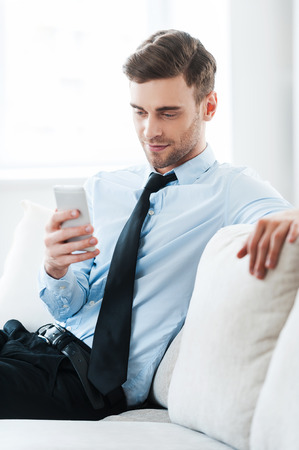 doing business: Feeling comfortable while doing business. Smiling young businessman holding mobile phone while sitting on sofa