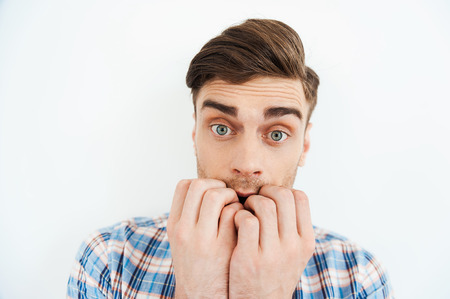 Feeling so scared. Nervous young man biting nails and looking at camera while standing against white background Stock Photo