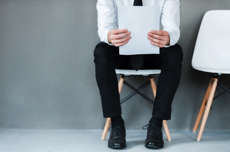 Waiting for interview. Close-up of young man holding paper while sitting on chair against grey background