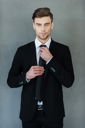 white suit: Used to look perfect. Handsome young businessman adjusting his necktie and looking at camera while standing against grey background