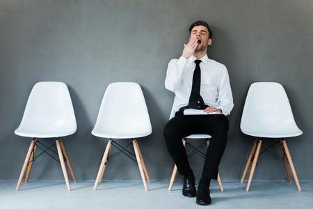 agotado: Cansado de esperar. Empresario joven cansado que sostiene el papel y que bosteza mientras estaba sentado en la silla contra el fondo gris