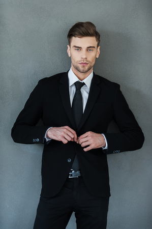standing businessman: Making business looking good. Handsome young businessman adjusting his jacket and looking at camera while standing against grey background